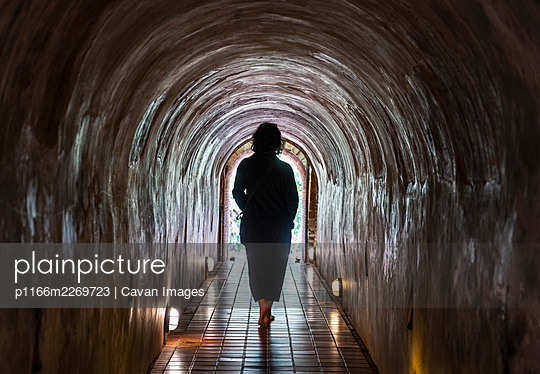 Woman walking through the tunnel's of the Temple Wat Umong - p1166m2269723 by Cavan Images