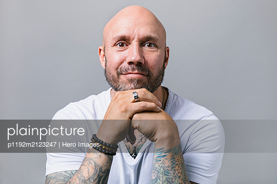 Portrait confident man with beard and tattoos - p1192m2123247 by Hero Images
