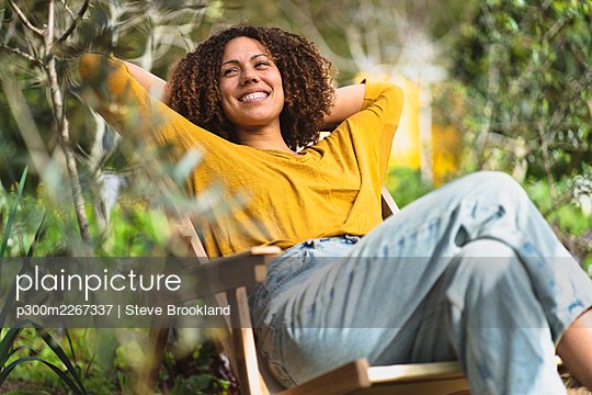 Smiling woman relaxing in garden chair in springtime in sustainable organic vegetable garden - p300m2267337 by Steve Brookland
