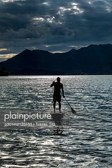 Silhouette man paddleboarding on sunny, idyllic lake, Walchensee, Bavaria, Germany - p301m2123153 by Tobias Titz