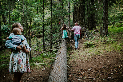 Father helping daughter walk on log while mom watches - p1166m2201930 by Cavan Images