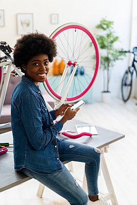 Smiling woman using mobile phone while sitting by bicycle on table at home - p300m2275889 by Giorgio Fochesato