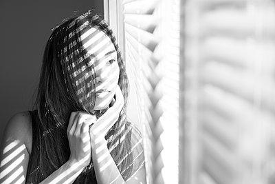 Asiatische Frau am Fenster  - p397m1515457 von Peter Glass