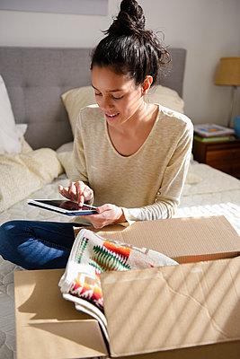 Hispanic woman sitting on bed near box using digital tablet - p555m1444107 by JGI/Jamie Grill