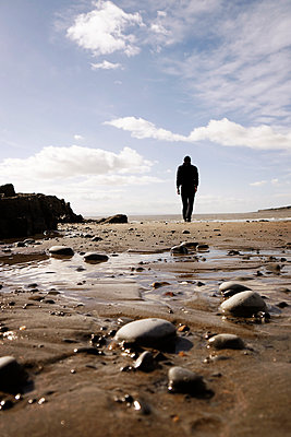 Rearview man walking over beach - p597m1488678 by Tim Robinson