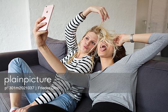 Zwei Mädchen auf dem Sofa - p1301m2021037 von Delia Baum
