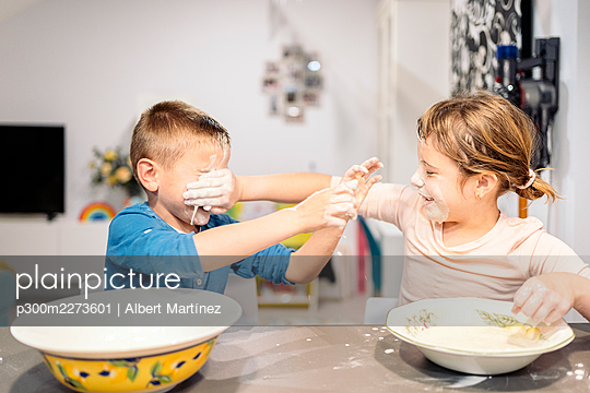 Playful siblings smearing faces with flour and water at home - p300m2273601 by Albert Martínez