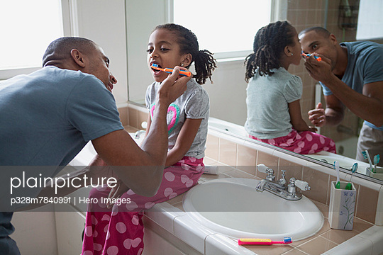 Dad brushing young daughter's teeth. - p328m784099f by Hero Images