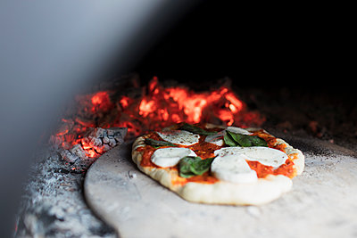 Close up homemade pizza on peel in pizza oven - p1023m2208349 by Sam Edwards