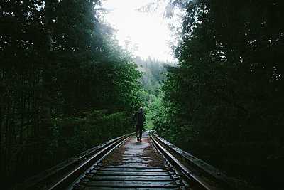 Rear view of man walking on railway tracks amidst trees - p1166m1534670 by Cavan Images