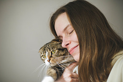 Young woman holding beautiful cat on white background - p1166m2255309 by Cavan Images