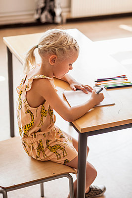Side view of girl drawing at desk in classroom - p1185m994145f by Astrakan