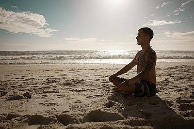 Mann meditiert auf dem Strand in der Abendsonne - p1640m2261021 von Holly & John