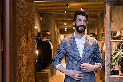 Portrait of smiling man wearing jacket leaving menswear shop - p300m2024017 by Josep Rovirosa