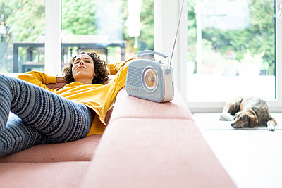 Woman lying on couch listening to music with portable radio at home - p300m2080495 von Joseffson