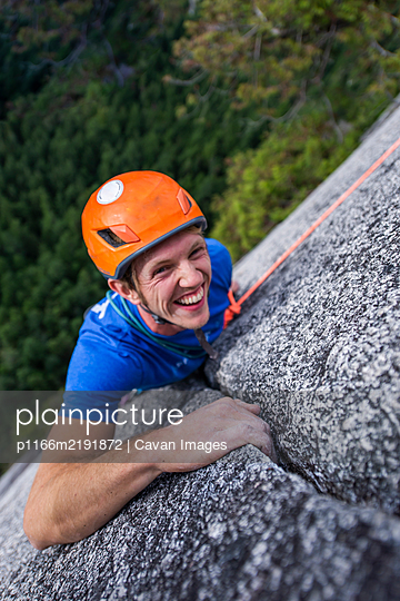climber looking up and laughing while rock climbing with helmet Chief - p1166m2191872 by Cavan Images