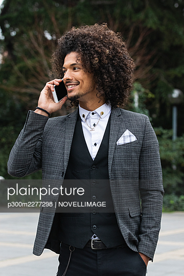 Smiling male professional with hand in pocket talking on smart phone - p300m2277298 by NOVELLIMAGE