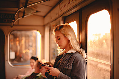 Young woman using smart phone while traveling in subway train - p1166m2153488 by Cavan Images