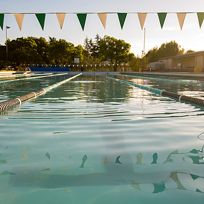 Lanes and flags at outdoor swimming pool - p1201m1039964 by Paul Abbitt