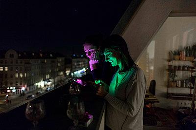 Zwei Mädels stehen mit Handy auf Balkon - p1301m1425886 von Delia Baum