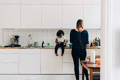 Full length of girl using smart phone while mother working in kitchen at home - p426m2097920 by Maskot