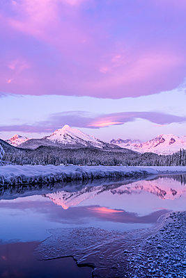 Alpenglow colours the snow-covered coastal range mountains, Mendenhall Glacier and Mendenhall towers are reflected in the open water along the edge of Auke Lake as the sun gets ready to set; Alaska, United States of America - p442m2074128 by John Hyde