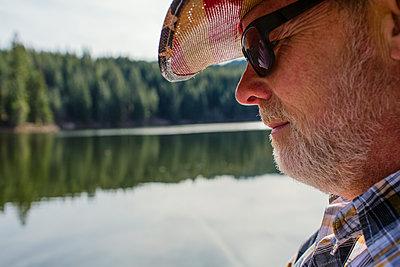 Close up of Caucasian man standing near lake - p555m1410099 by Eric Raptosh Photography