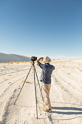 Caucasian photographer with tripod in desert - p555m1523051 by Marc Romanelli