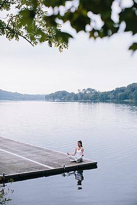 Yoga am See, Frau sitzt in der Lotos-Position - p586m956093 von Kniel Synnatzschke