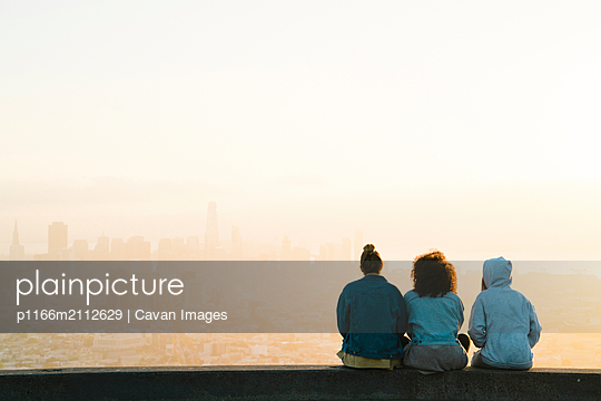 Rear view of female friends looking at cityscape while sitting against sky during sunset - p1166m2112629 by Cavan Images