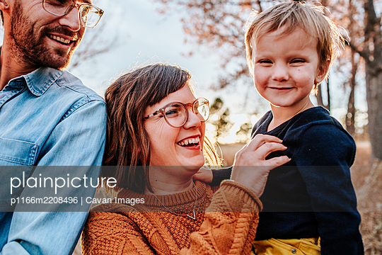 Smiling parents tickling young son outside on a fall evening - p1166m2208496 by Cavan Images