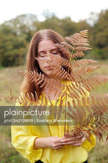 Teenage girl in yellow blouse holding fern in hand - p1412m2128859 by Svetlana Shemeleva
