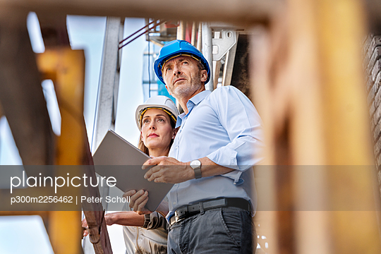 Male architect holding digital tablet while examining construction site with colleague - p300m2256462 by Peter Scholl