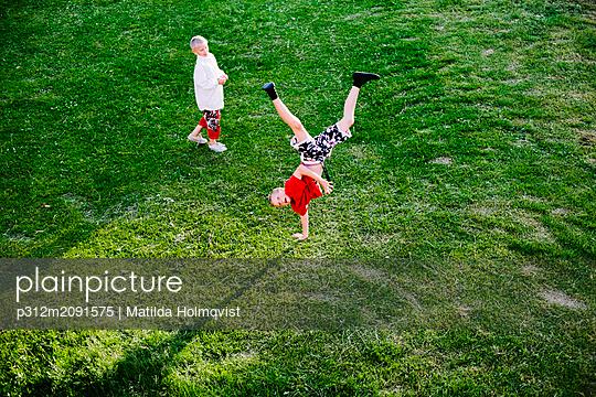 Boy doing handstand - p312m2091575 by Matilda Holmqvist