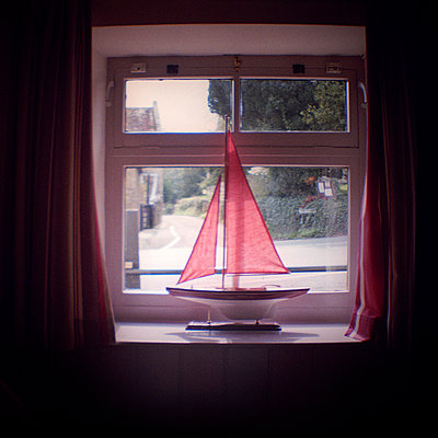 Model boat in sunlit window - p1072m829380 by Neville Mountford-Hoare