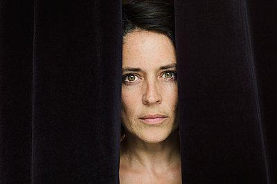 Woman between black curtain, portrait - p1150m2158828 by Elise Ortiou Campion