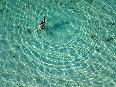 Indonesia, Bali, Melasti, Aerial view of Karma Kandara beach, one woman in water - p300m2042539 by Konstantin Trubavin