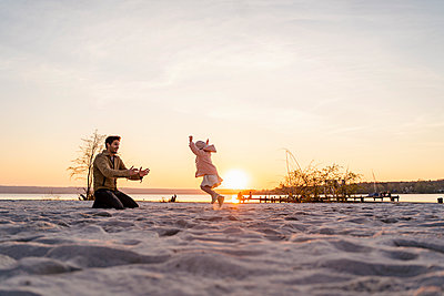 Germany, Bavaria, Herrsching, father and daughter playing on the beach at sunset - p300m2102738 by Daniel Ingold