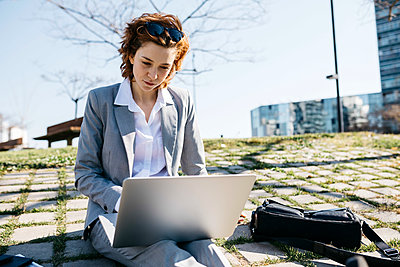 Businesswoman in the city, sitting on ground, working on laptop - p300m2103925 by Josep Rovirosa