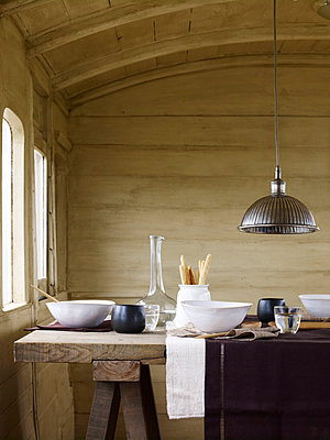 Metal pendant light above trestle with ceramic bowls and glassware - p349m2167719 by Polly Wreford