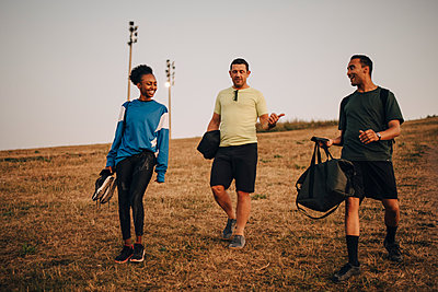 Smiling male and female athlete walking on grassy land during sunset - p426m2270729 by Maskot