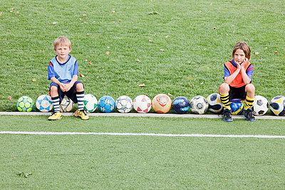 Caucasian children sitting with soccer balls - p555m1479569 by Ronnie Kaufman/Larry Hirshowitz