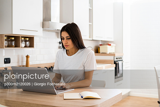 Young woman using laptop at home - p300m2120026 by Giorgio Fochesato