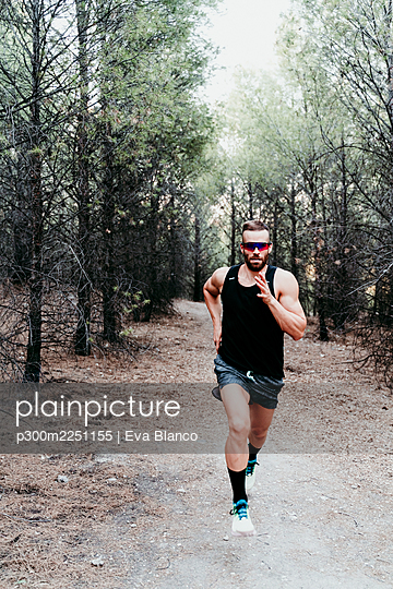 Handsome male athlete running on mountain trail in forest - p300m2251155 by Eva Blanco