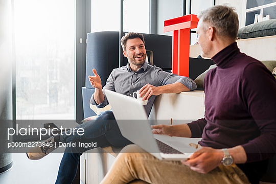Smiling businessman discussing with male colleague with laptop at work place - p300m2273946 by Daniel Ingold