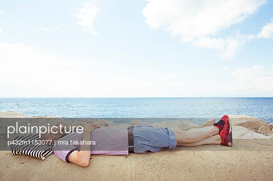Mann schläft am Meer - p432m1153077 von mia takahara
