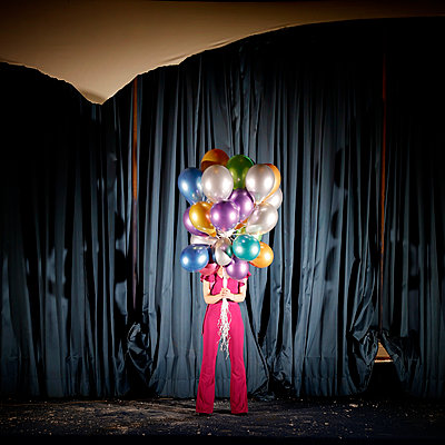 Woman with colourful balloons in front of stage curtain - p1105m2254504 by Virginie Plauchut