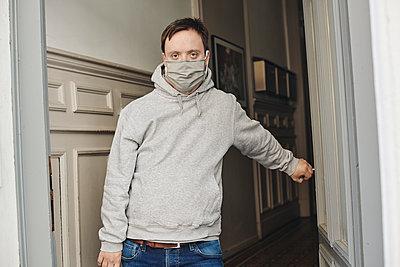 Mann mit Mundschutz im Hausflur - p1164m2177962 von Uwe Schinkel