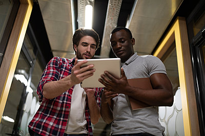 Multiethnic colleagues using tablet in office hallway - p1166m2234883 by Cavan Images