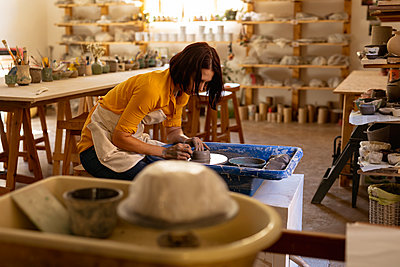 Female potter in a pottery studio using pottery wheel - p1315m2130890 by Wavebreak